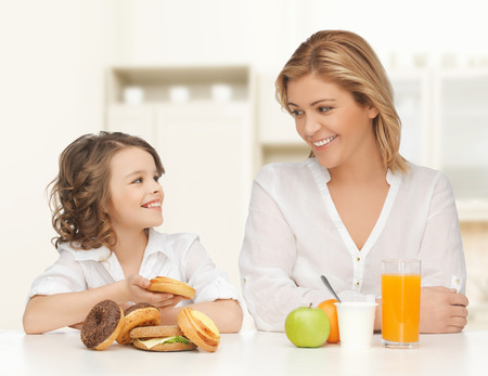 people, healthy lifestyle, family and unhealthy food concept - happy mother and daughter eating different food over home kitchen background photo