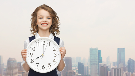 people, time management and children concept - smiling girl holding big clock showing 8 oclock over city background Stock Photo