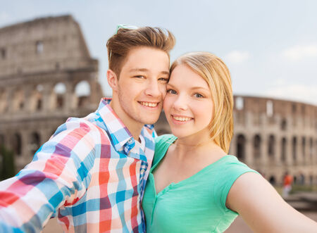 teenage couple: travel, tourism, technology, people and love concept - smiling couple with smartphone or camera taking selfie over coliseum background