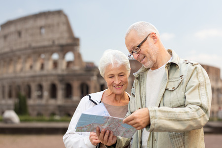 family, age, tourism, travel and people concept - senior couple with map and city guide on street over coliseum background Stockfoto