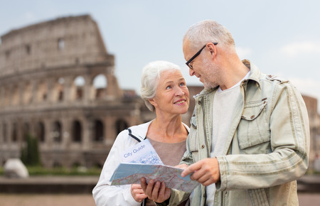 family, age, tourism, travel and people concept - senior couple with map and city guide on street over coliseum background photo