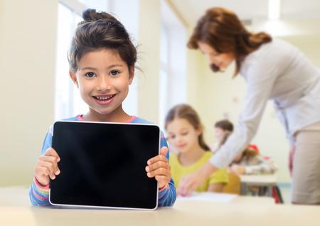 교육, 초등학교, 기술, 광고 및 어린이 개념 - 교실과 급우 배경 위에 빈 검은 태블릿 pc 컴퓨터 화면을 보여주는 작은 학생 소녀