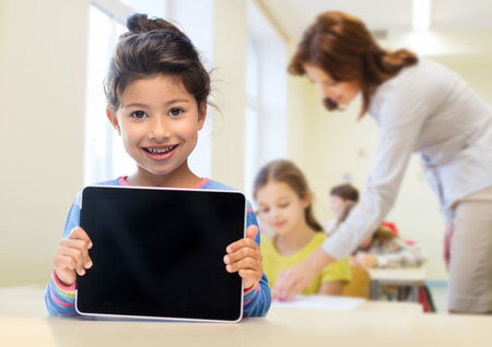 education, elementary school, technology, advertisement and children concept - little student girl showing blank black tablet pc computer screen over classroom and classmates background Imagens