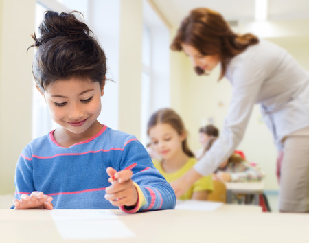 education, elementary school and children concept - happy little student girl with pen and paper writing over classrom and teacher background Banque d'images