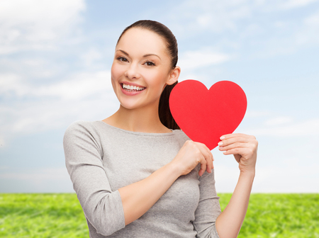 happiness, love and health concept - smiling asian woman with red heart photo