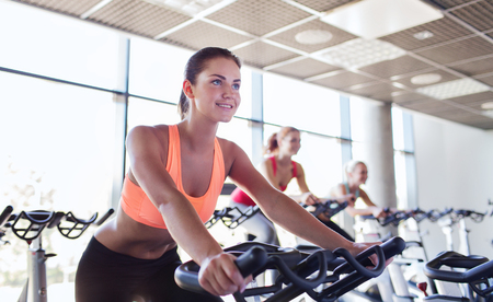 cardio fitness: sport, fitness, lifestyle, equipment and people concept - group of women riding on exercise bike in gym
