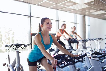 sport, fitness, lifestyle, apparatuur en mensen concept - groep vrouwen rijden op hometrainer in de sportschool Stockfoto
