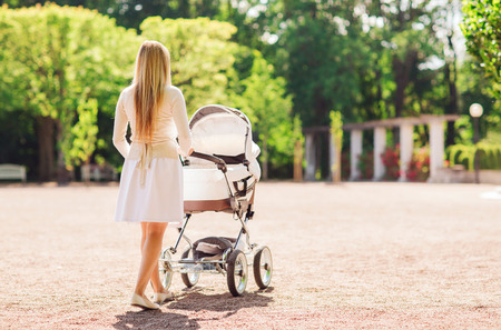 child care: family, child and parenthood concept - happy mother walking with baby stroller in park from back Stock Photo