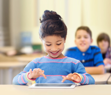 schooltime: education, elementary school, technology and children concept - happy little student girl with tablet pc over classroom and classmates background