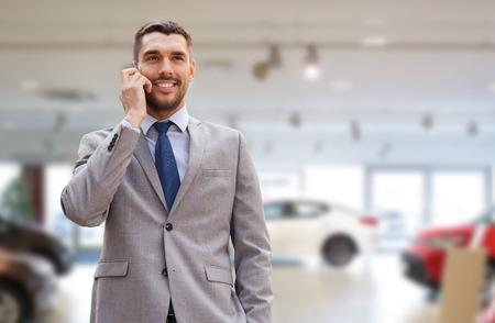 自動車事業、車販売、ジェスチャーおよび人々 のコンセプト - 自動ショーの背景にスマート フォンで話しているビジネスマンを笑顔 写真素材