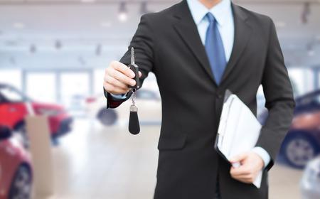activité automobile, vente voiture, le geste et les gens notion - gros plan homme d'affaires ou un vendeur, documents donnant clé de voiture sur Auto Show fond