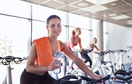 sport, fitness, lifestyle, equipment and people concept - group of women with water bottle riding on exercise bike in gym photo