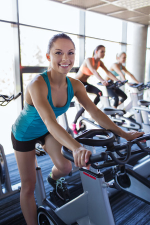 cardio workout: sport, fitness, lifestyle, equipment and people concept - group of women riding on exercise bike in gym