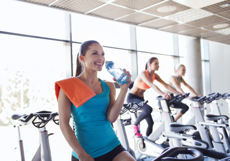 cardio fitness: sport, fitness, lifestyle, equipment and people concept - group of women with water bottle riding on exercise bike in gym Stock Photo
