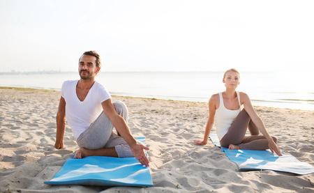 yoga beach: fitness, sport, friendship and lifestyle concept - couple making yoga exercises sitting on mats outdoors