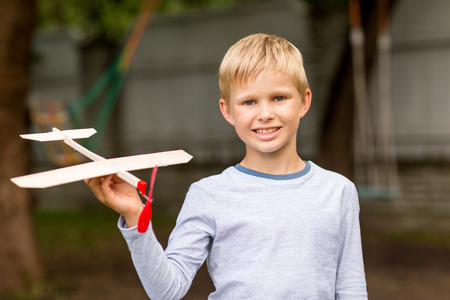 dreams, future, hobby, people and childhood concept - smiling little boy holding wooden airplane model in his hand outdoors photo