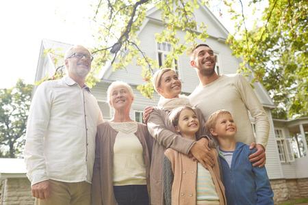 Familie, geluk, generatie, thuis en mensen concept - gelukkige familie staan voor huis buiten Stockfoto