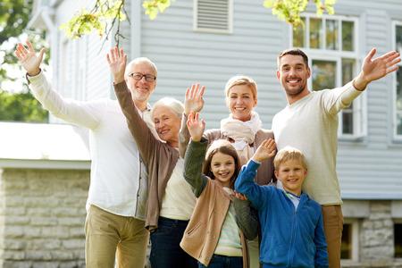personas saludando: gesto, la felicidad, la generaci�n, el hogar y las personas concepto - familia feliz agitando las manos delante de la casa al aire libre Foto de archivo