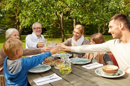 familj, generation, hem, semester och folk koncept - lycklig familj middag och klirrande glas i sommarträdgård Stockfoto