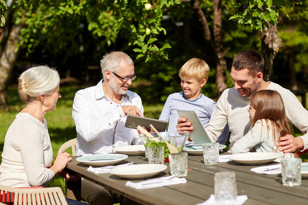 family, generation, technology, home and people concept - happy family with tablet pc computers sitting at table in summer garden Stockfoto