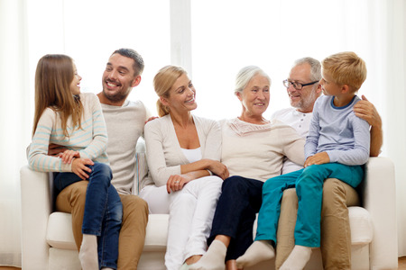 family  room: family, happiness, generation and people concept - happy family sitting on couch at home