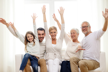 family sofa: family, happiness, generation and people concept - happy family sitting on sofa and rising hands at home Stock Photo