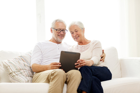 man woman hugging: family, technology, age and people concept - happy senior couple with tablet pc computer at home