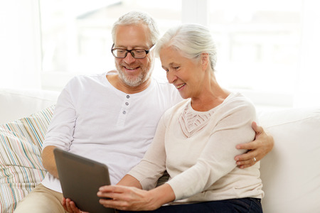 old man sitting: family, technology, age and people concept - happy senior couple with tablet pc computer at home