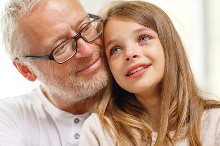 abuelo: la familia, el apoyo, la infancia y las personas concepto - abuelo con nieta llorando en casa