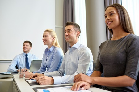 developers: business, people and conference concept - smiling business team meeting on presentation in office Stock Photo