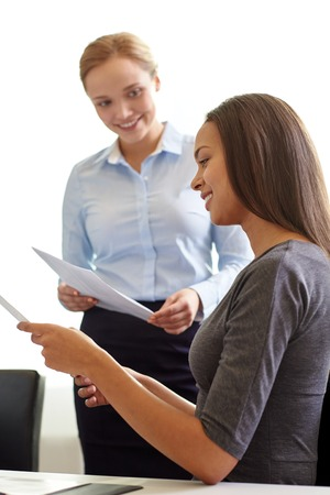business, people and teamwork concept - smiling businesswomen with papers talking in office photo
