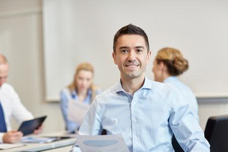 het bedrijfsleven, mensen en teamwork concept - lachend zakenman met de groep van ondernemers bijeenkomst in kantoor
