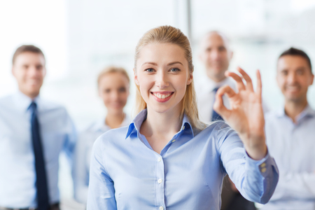 ok: business, people, gesture and teamwork concept - smiling businesswoman showing ok sign with group of businesspeople in office
