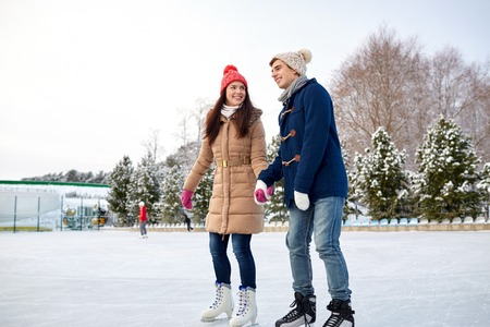 ice arena: people, winter, friendship, sport and leisure concept - happy couple ice skating on rink outdoors