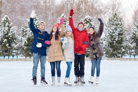 wave: people, winter, friendship, sport and leisure concept - happy friends ice skating and waving hands on rink outdoors