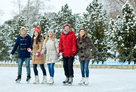ice arena: people, winter, friendship, sport and leisure concept - happy friends ice skating on rink outdoors Stock Photo