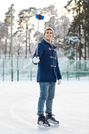iceskates: people, winter, technology and leisure concept - happy young man taking picture with smartphone selfie stick on ice skating rink outdoors
