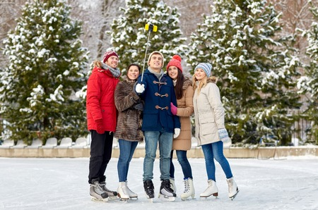 people, friendship, technology and leisure concept - happy friends taking picture with smartphone selfie stick on ice skating rink outdoors photo