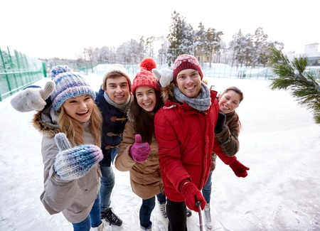 people, friendship, technology and leisure concept - happy friends taking picture with smartphone selfie stick and showing thumbs up on ice skating rink outdoors