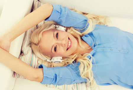 free time: technology, music and happiness concept - smiling young girl lying on sofa in headphones at home Stock Photo