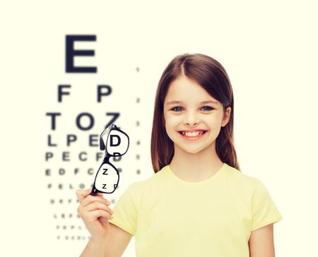 eye exam: education, school and vision concept - smiling cute little girl holding black eyeglasses
