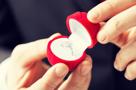 proposal of marriage: man making proposal with wedding ring and gift box.