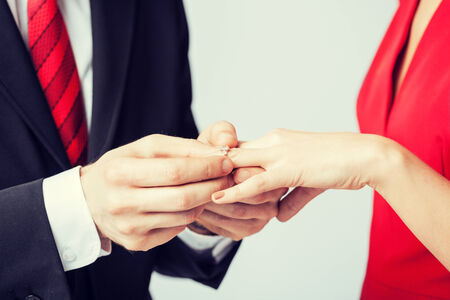 wedding ring hands: picture of man putting  wedding ring on woman hand Stock Photo