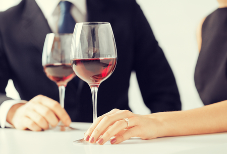 proposing: picture of engaged couple with wine glasses in restaurant Stock Photo