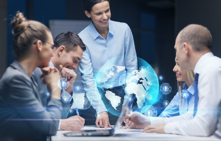 hologram: global business, technology, management , connection and people concept - smiling female boss talking to business team in office Stock Photo