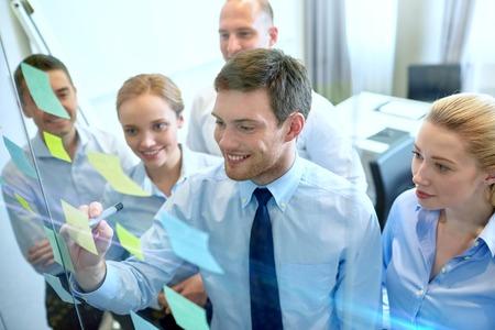planificacion: negocios, personas, trabajo en equipo y la planificación concepto - sonriendo equipo de negocios con marcador y pegatinas que trabaja en oficina