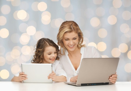 people, technology, family and parenthood concept - happy mother and daughter with laptop and tablet pc computers sitting at table over holidays lights background photo
