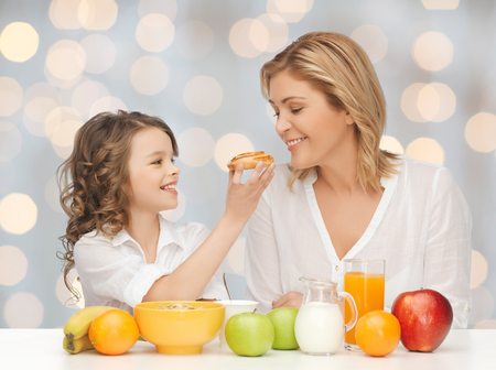 people, healthy lifestyle, family and food concept - happy mother and daughter eating healthy breakfast over holidays lights background photo