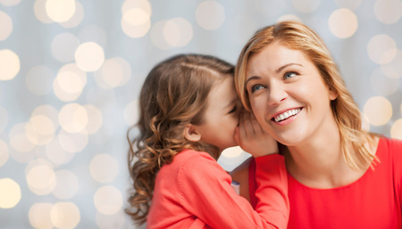 people, trust, love, family and motherhood concept - happy daughter whispering gossip to her mother over holiday lights background Foto de archivo