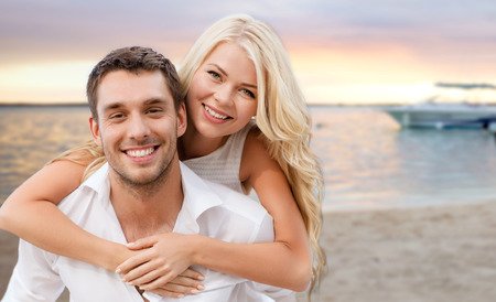 summer holiday, vacation, dating and travel concept - happy couple having fun over tropical beach background photo